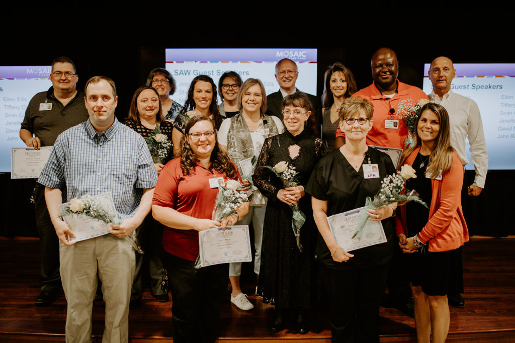 """Mosaic Life Care School at Work, 2019 Graduates.  15 people are standing clustered together holding flowers and certificates. They are standing in front of three projection screens showing """"SAW Guest Speakers"""" at their graduation ceremony."""